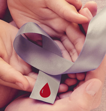 Group of hands holding a silver ribbon with a blood drop on it.