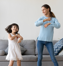 A mother and daughter dancing together at home