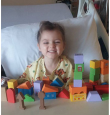 Adrianna in her hospital bed playing with blocks.