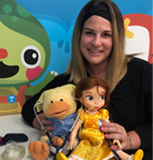 Allison Butler, child life specialist, holding a doll