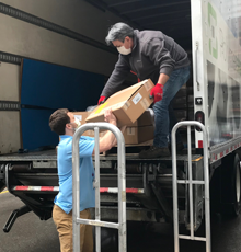 Two men unloading a truck full of donations