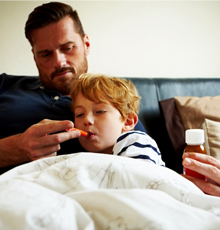 Dad taking his son's temperature in bed