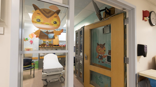 Pediatric emergency department room with illustrations of Toughlings on the door and window